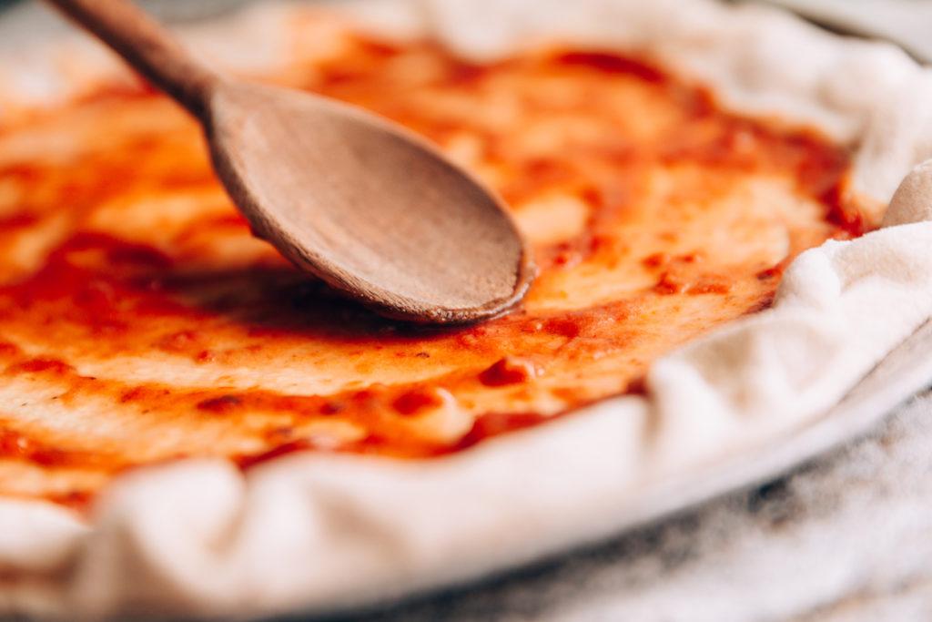 Spreading tomato sauce on pizza pan