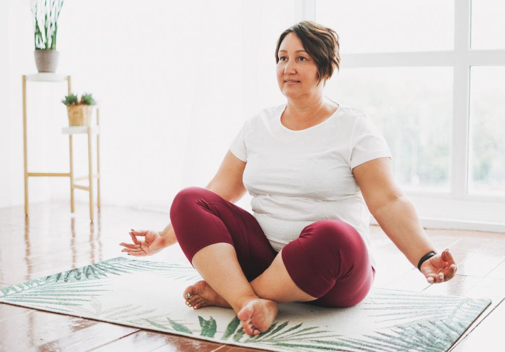 Adult woman practicing yoga at bright studio
