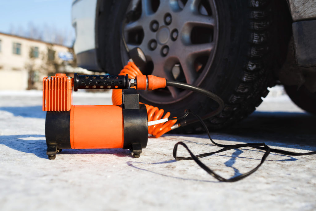 Car air compressor inflating tire outside