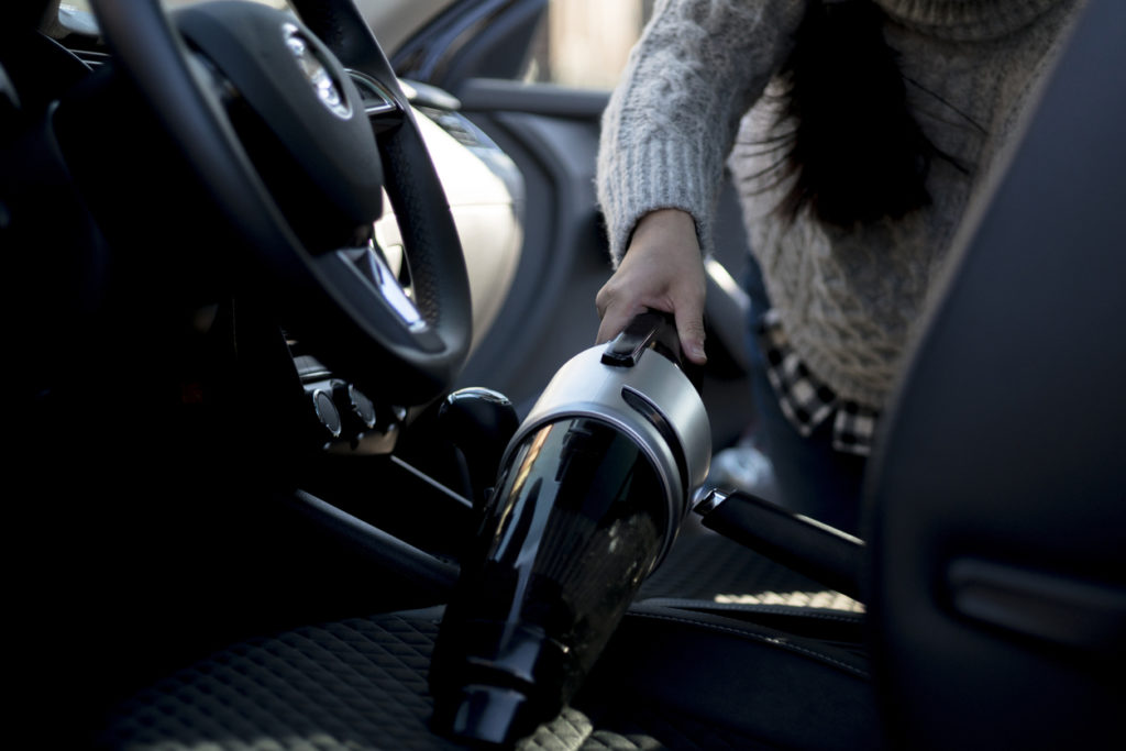 cleaning car interior with portable vacuum cleaner